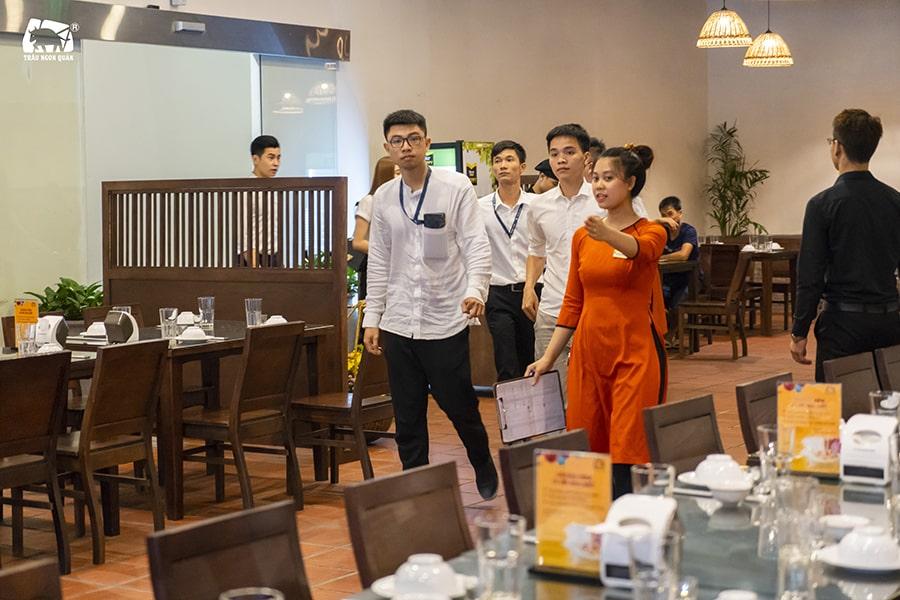 Nhân viên lễ tân chỉ dẫn khách vào bàn ăn